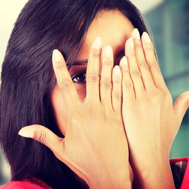 Anonymer Test: Frau bedeckt ihr Gesicht mit den Händen