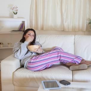 Essen aus Langeweile: Frau sitzt auf einer Couch und isst Popcorn