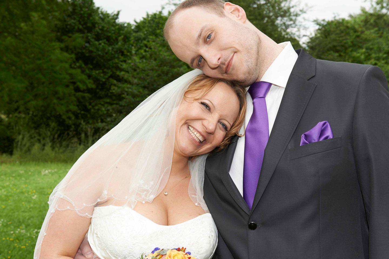 Hochzeit auf den ersten Blick: Brautpaar steht gegeneinander gelehnt auf der Wiese