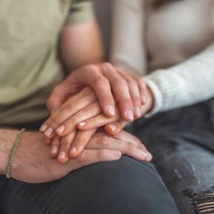 Verzeihen: Ein Pärchen legt die Hände aufeinander auf das Bein des Mannes