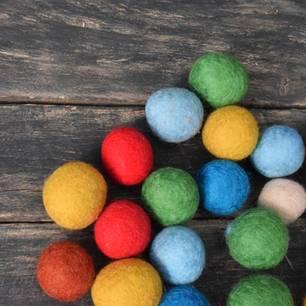 Filzen mit Kindern: Filzkugeln auf Holzuntergrund