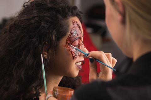 Narben schminken: Visagistin schminkt Frau Narben ins Gesicht