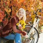 Horoskop: Eine glückliche Frau vor einer Herbsthecke mit Sonnenblumen in der Hand
