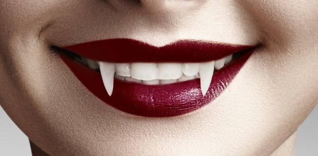 Vampir schminken: Frau mit roten Lippen und Vampir-Zähnen
