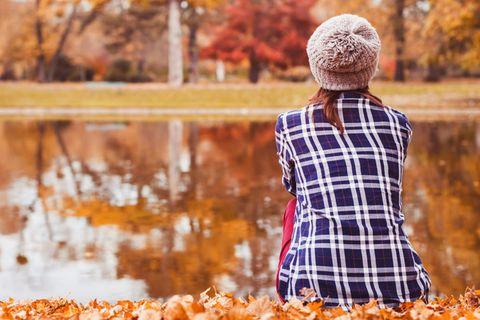 30 und kinderlos: Frau sitzt am See