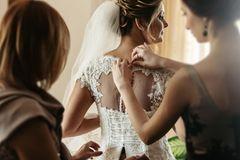 Braut zieht ihr Brautkleid an