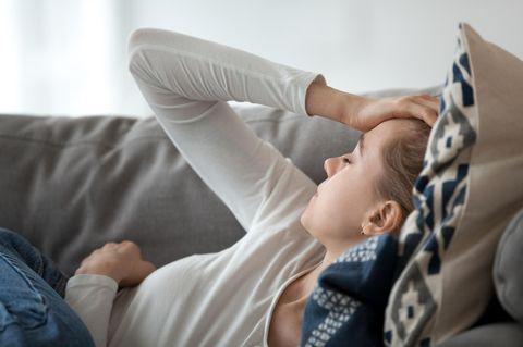 Spannungskopfschmerzen: Frau liegt auf dem Sofa