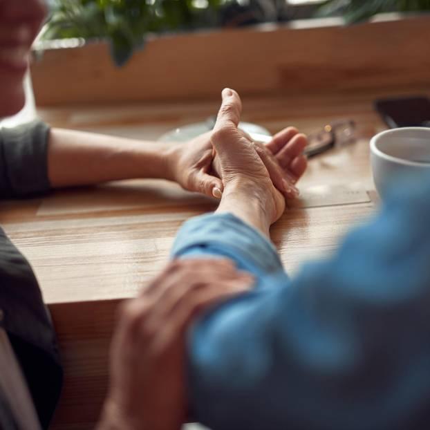 Umgang mit Alzheimer - wenn die Freundin plötzlich vergisst: Junge Dame hält älterer Dame die Hand