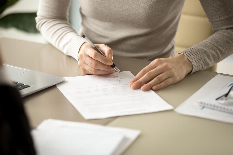 Unterschrift bei Online-Bewerbungen: Frau unterschreibt Dokument