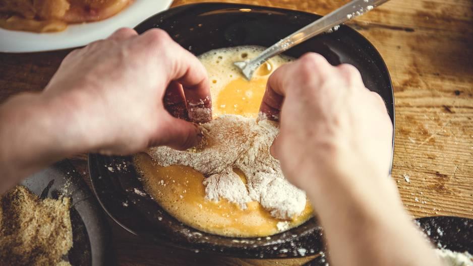 Panieren: Fleisch wird in Eigelb getunkt