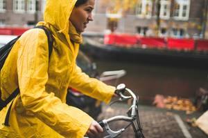 Frau in Regenmantel auf Fahrrad im Regen