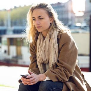Horoskop: Eine zögerliche Frau mit einem Handy in der Hand
