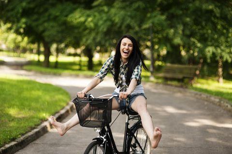Gute-Laune-Fakten: Eine fröhliche junge Frau auf dem Fahrrad