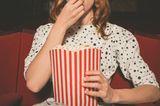 Liebeskummertipps der Redaktion: Eine Frau im Kino mit Popcorn in der Hand