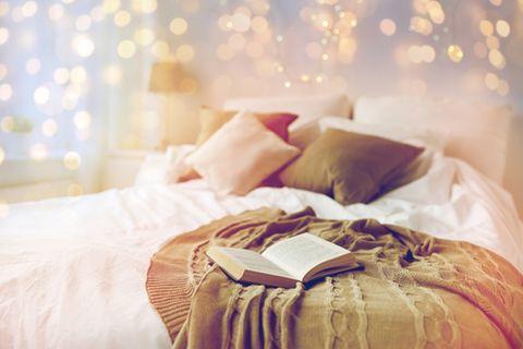 Lichterketten: Buch liegt auf einem Bett, darüber leuchtet eine Lichterkette