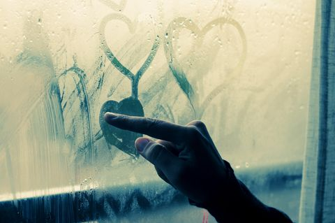 Liebeskummertipps der Redaktion: Eine Frau zeichnet Herzen an eine beschlagene Scheibe