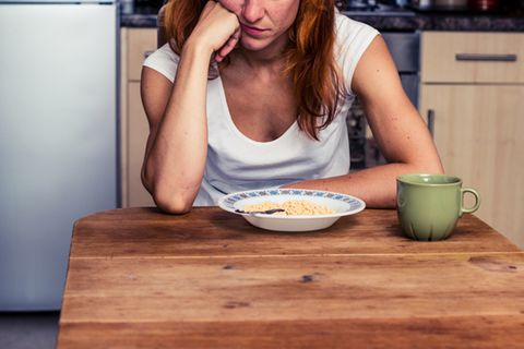 Appetitlosigkeit: Frau sitzt am Esstisch und schaut gelangweilt aufs Essen