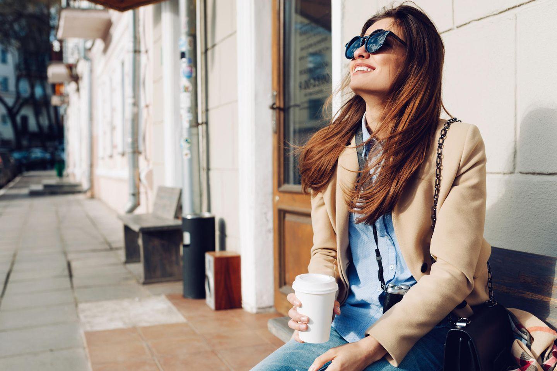 5-Minuten-Pause: Eine entspannte Frau mit Kaffee und Sonnenbrille