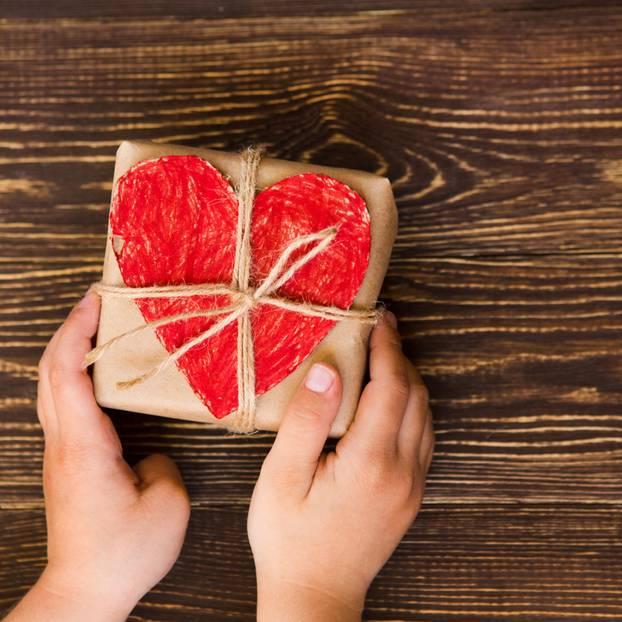 Besser spenden: Kind hält Paket mit Herz in den Händen