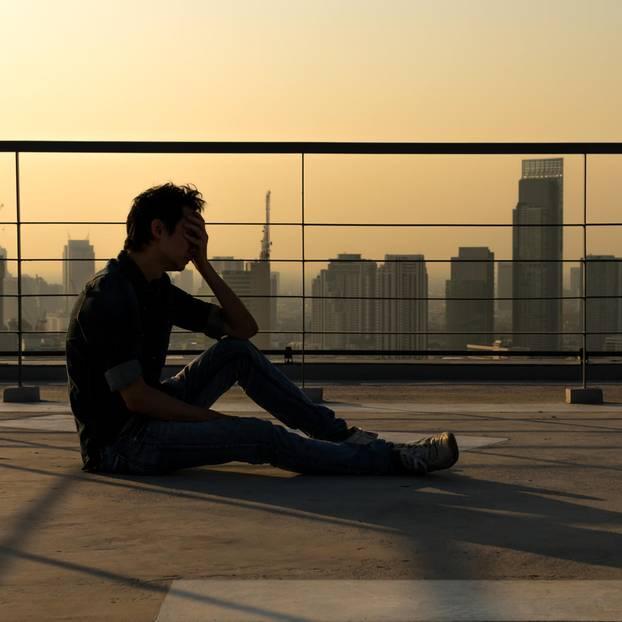 Horoskop: Ein trauriger Mann sitzt auf einem Dach
