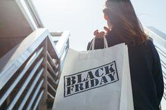 Black Friday: Die besten Spartipps: Frau hält Black Friday Tüte in der Hand