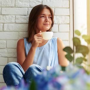 Eisenhower-Prinzip: Eine junge Frau sitzt auf der Fensterbank und trinkt einen Tee