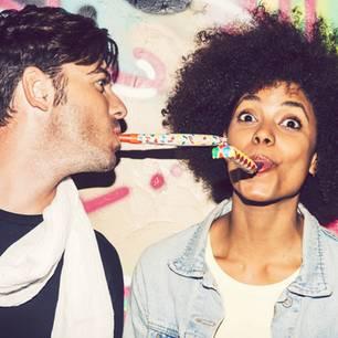 """""""Wer würde eher""""-Fragen: 77 lustige Ideen! Zwei junge Leute mit Partytröte"""
