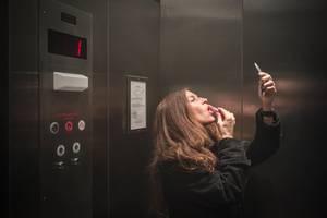 Partnersuche ab 50: Fast unmöglich?: Frau schminkt sich mit Handspiegel im Fahrstuhl