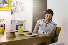 Alleine, aber glücklich - entdecke dich selbst: Frau trinkt Kaffee und liest Zeitung