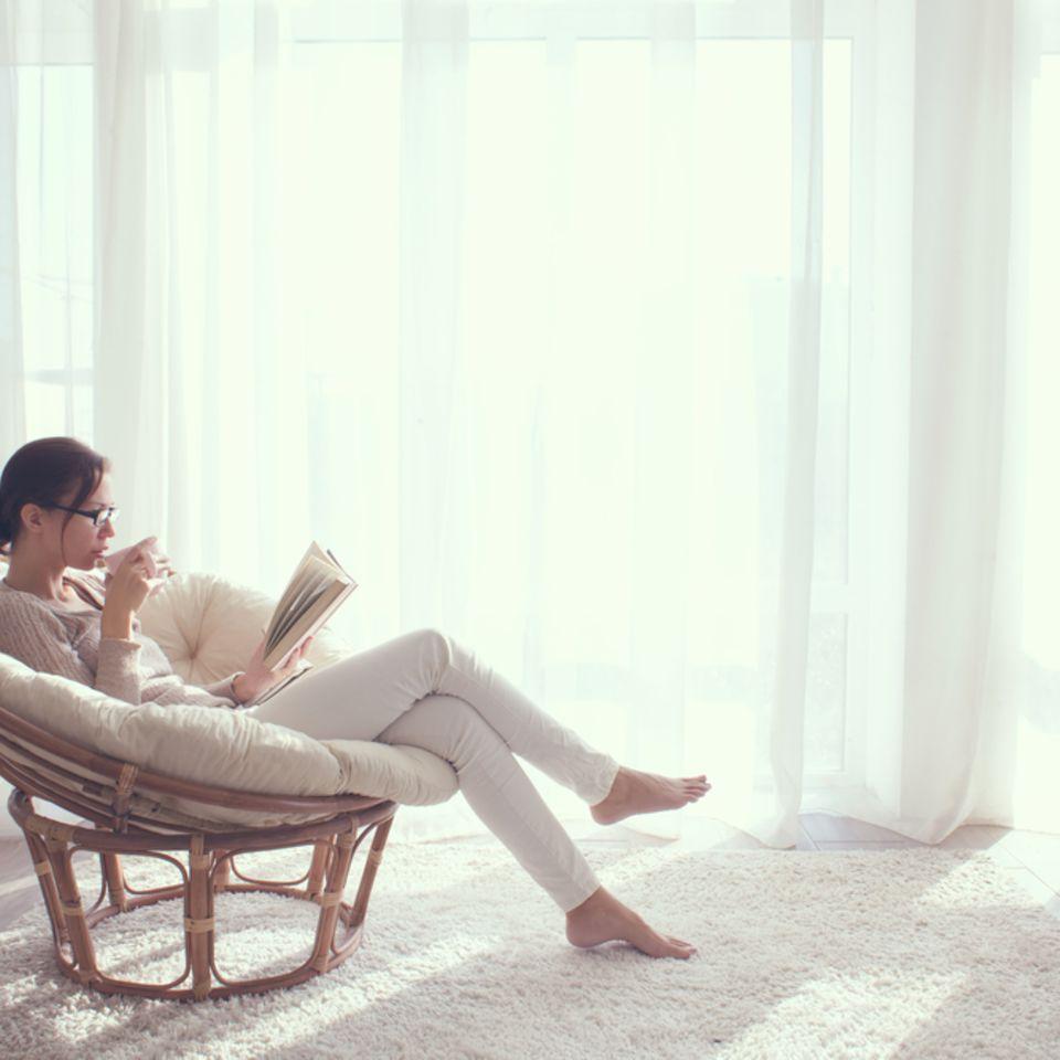 Mehr Zeit für mich: Frau sitzt im Stuhl und liest ein Buch