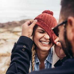 Horoskop: Ein Mann zieht seiner lachenden Freundin die Mütze schief