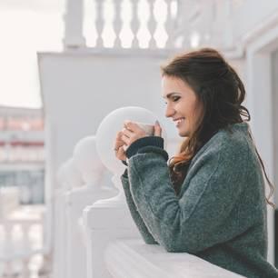 Horoskop: Eine fröhliche Frau im Winter auf dem Balkon