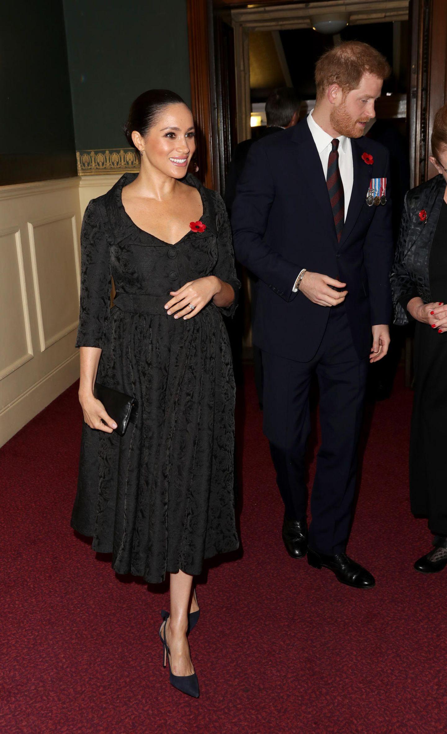 Strahlend wie immer erschienen Prinz Harry und seine Meghan zu den Feierlichkeiten im Rahmen des Rembrance Days in der Royal Albert Hall. Meghan setzte dazu auf ein schwarzes, weit ausgestelltes Kleid im 50er-Jahre-Stil sowie ihre obligatorischen schwarzen Pumps. Doch das bestickte Kleid war nicht der einzige Blickfang an diesem Abend. Meghans Hand bot Raum für Spekulationen – immer wieder wanderte sie zu ihrem Bauch und heizte damit die Gerüchte um eine zweite Schwangerschaft an. Der Schnitt des Kleides sowie Meghans entwaffnendes Strahlen taten ihr übriges, um die Fans auf erneuten Nachwuchs hoffen zu lassen.