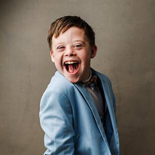 Down-Syndrom: Junge schaut in die Kamera und lacht