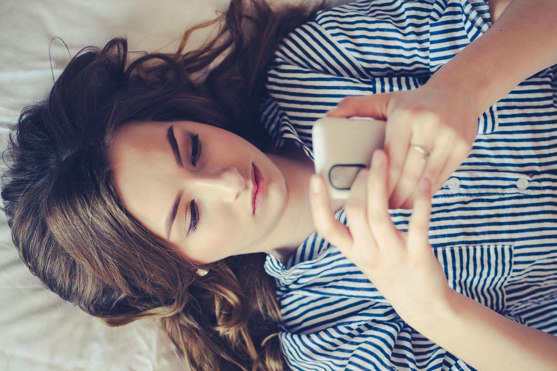 FOMO: Eine traurige Frau mit einem Handy in der Hand