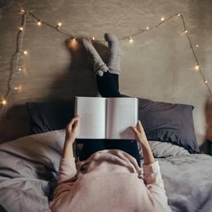 Gemütlichkeit: Frau liegt im Bett und liest