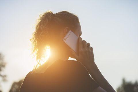 Emotional intelligent: Frau telefoniert im Sonnenuntergang