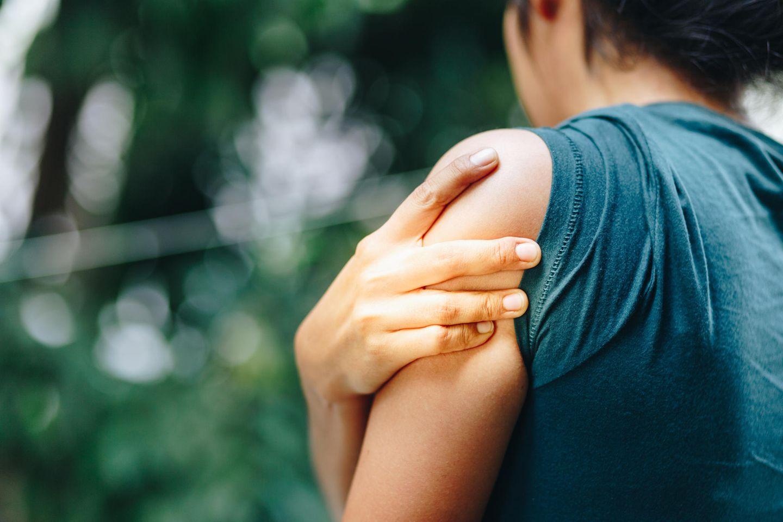Gliederschmerzen: Frau hält sich den Oberarm