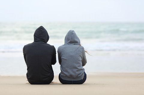 Beziehungskrise: Ein Paar sitzt nebeneinander, ohne sich zu berühren, am Meer