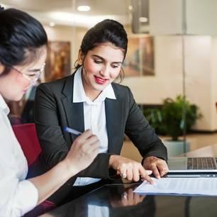 Stärken in der Bewerbung: Frau geht mit Kollegin Dokumente durch
