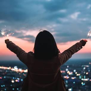 Horoskop: Eine Frau mit Wunderkerzen im Sonnenuntergang