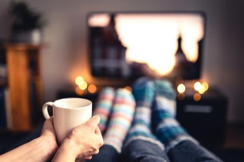 Winterfilme: Paar schaut TV mit Becher in der Hand
