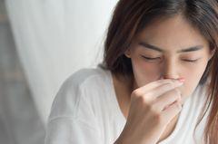 Kalte Nase: Frau fasst sich an die Nase