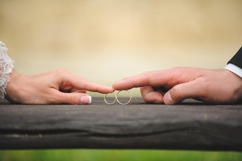 Whisper: Eine Männerhand und eine Frauenhand rollen je einen Ehering über den Tisch