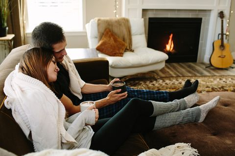 Horoskop: Ein Pärchen auf der Couch vor dem Kamin