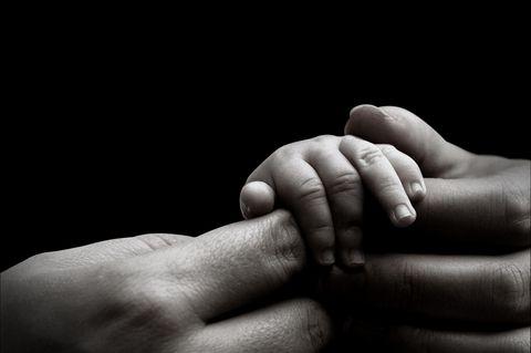 Unbemerkt schwanger: Mutter hält Babyhand