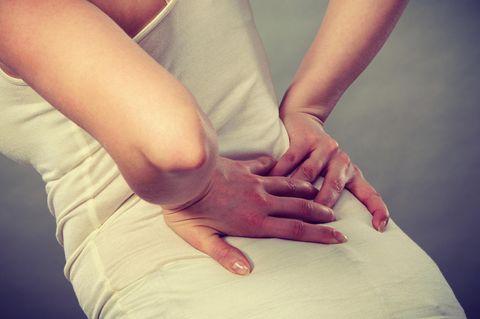 Kreuzschmerzen: Frau hält sich den Rücken