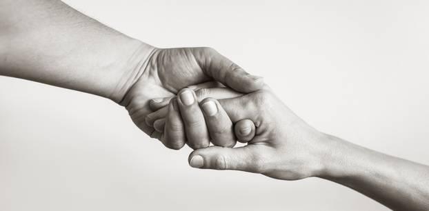Trösten: Zwei Menschen halten ihre Hände