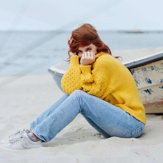 Horoskop: Eine junge Frau in gelbem Wollpulli am Meer