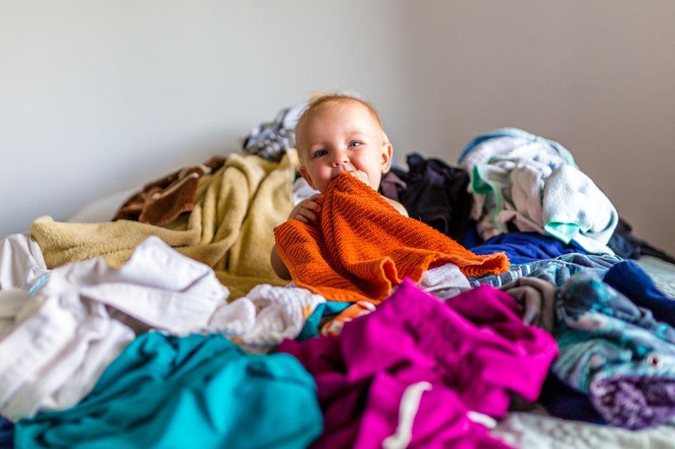 Baby zwischen Wäschebergen
